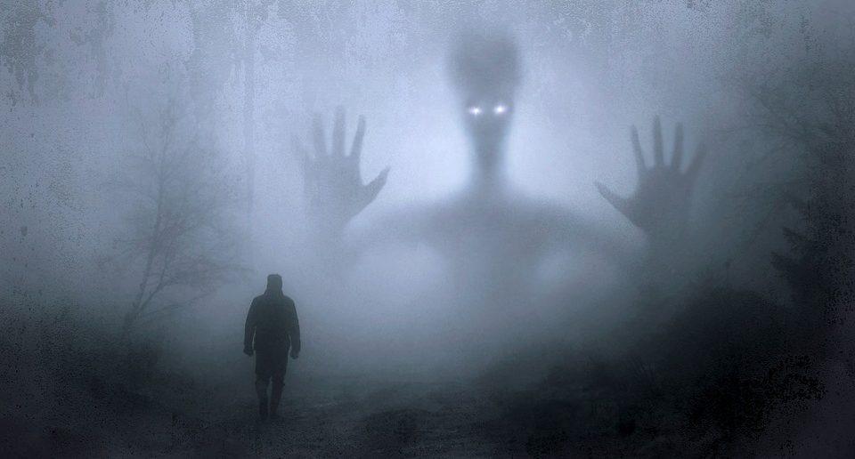 A man walking in fog towards a ghostly figure