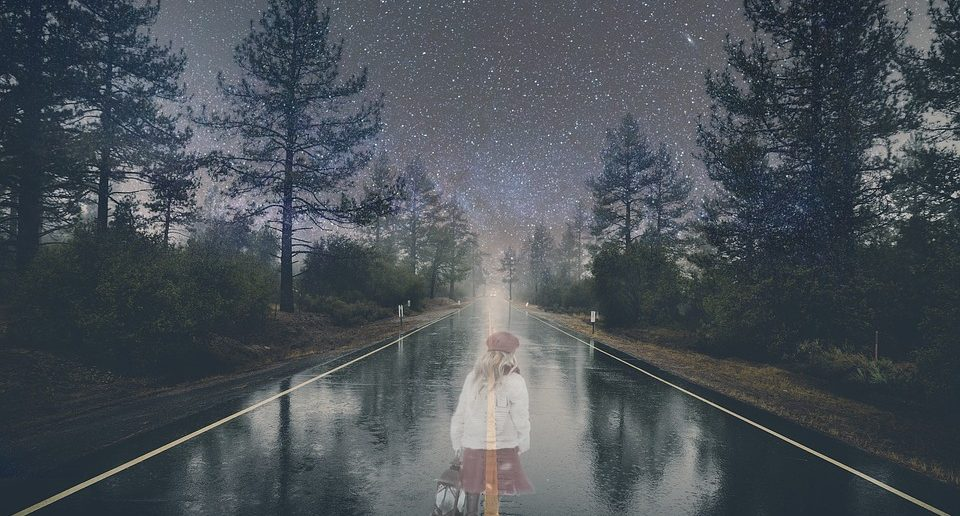 A ghostly figure of a young girl on an empty road