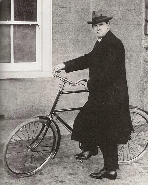 Michael Collins holding a bicycle