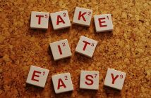 scrabble letters on corkboard saying take it easy