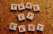 scrabble letters on corkboard saying take it easy