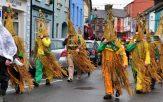 wren boys in costume parading through a street