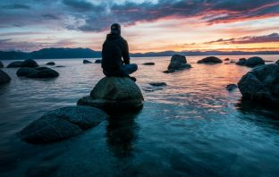 person sitting on a rock looking at a sunset scene
